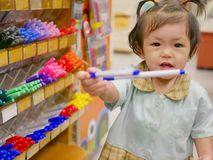 Little Asian baby girl taking color pens from the shelves. Little Asian baby girl, 18 months old, taking color pens from the shelves in a stationary shop stock image