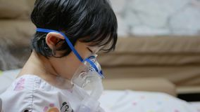 Little Asian baby girl wearing a respiratory face mask and inhaling medicine, mist, from a nebulizer