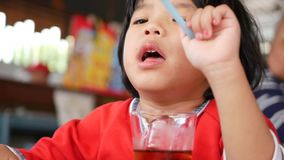 Little Asian baby girl playing a pen while drinking soda pop - baby`s exploration of things around them.  stock footage