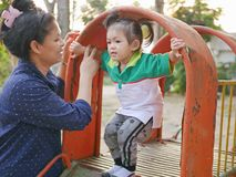 Little Asian baby girl playing a slide with help from her mother - mother daughter relationship stock photos