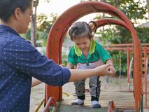 Little Asian baby girl playing a slide with help from her mother - mother daughter relationship royalty free stock photos
