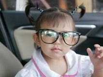 Little Asian baby girl putting on eyeglasses. Baby`s curiosity royalty free stock images