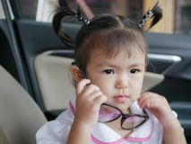 Little Asian baby girl putting on eyeglasses. Baby`s curiosity royalty free stock photos