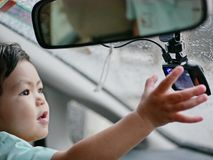 Little Asian baby girl reaching out catching a car`s front camera. Little Asian baby girl reaching out and catching a car`s front camera on a rainy evening Royalty Free Stock Images