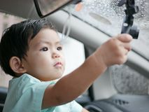 Little Asian baby girl reaching out catching a car`s front camera. Little Asian baby girl reaching out and catching a car`s front camera on a rainy evening Stock Image