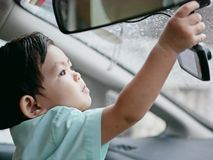 Little Asian baby girl reaching out catching a car`s front camera. Little Asian baby girl reaching out and catching a car`s front camera on a rainy evening Royalty Free Stock Photo