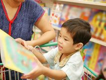 Little Asian baby girl in a shopping trolley being happy choosing a book stock image