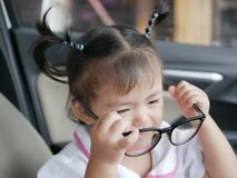 Little Asian baby girl taking off eyeglasses, after trying to put them on. Baby`s curiosity royalty free stock photography