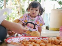 Little Asian baby girl watching her mother putting hot dogs on each wooden stick. Involving baby in meal preparation creates family bonds and helps them learn stock images
