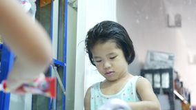 Little Asian baby girl, 3 years old, learning to squeeze out the toothpaste onto her toothbrush and close the cap by herself. Baby`s fine motor learning for stock video footage