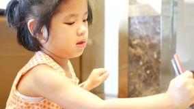 Little Asian baby girl, 3 years old, learning to use / hold chopsticks to cook a hotpot by herself.  stock footage