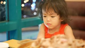 Little Asian baby girl, 2 years old, paying no attention to the meal, losing appetite, as she was addicted to a smartphone