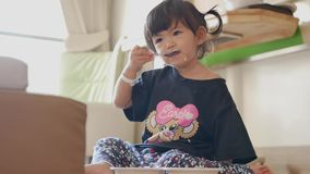 Little Asian baby girls enjoys eating / playing with her meal by herself. Little Asian baby girls, 22 months old, enjoys eating / playing with her meal by stock video footage