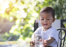 Little asian baby going to drink water in a glass cup in the mor. Ning time with nature bokeh background royalty free stock photos