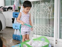 Little Asian baby holding water hose while washing clothes at home. Little Asian baby holding water hose to fill water into a bucket while washing clothes at stock image