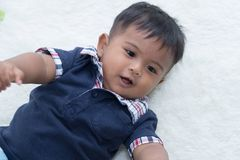 Cute little asian baby lying on soft blanket royalty free stock photography