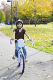 Little Asian biracial girl riding bike in park. Little girl riding bike in park in late summer, early autumn Royalty Free Stock Photo