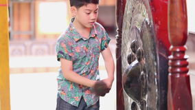 Little asian boy bangs on a large Antique Thai Gong( Bell) stock video footage