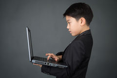 Little asian boy in black suit with laptop Royalty Free Stock Image