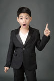 Little asian boy in black suit point up Royalty Free Stock Photography