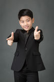 Little asian boy in black suit pointing finger to the front Stock Photos