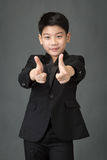 Little asian boy in black suit pointing finger to the front Stock Images