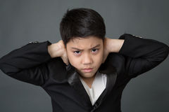 Little asian boy in black suit upset, depression face Royalty Free Stock Images