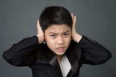 Little asian boy in black suit upset, depression face Royalty Free Stock Photos
