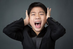 Little asian boy in black suit upset, depression face Stock Image