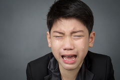 Little asian boy in black suit upset, depression face. On gray background Royalty Free Stock Photography
