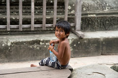 Little asian boy with bottle of water posing in Angkor Wat templ Royalty Free Stock Images
