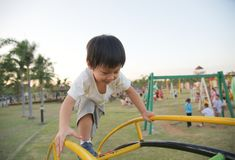 Little boy climbs up the ladder on playground. Little asian boy climbs up the ladder on playground Royalty Free Stock Images