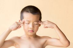 A little asian boy doing sad and do not wear a shirt. He standing near a old cement wall Stock Images