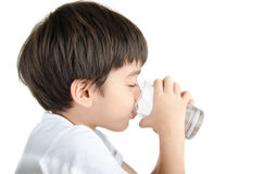 Little asian boy drinks water from a glass on white background Royalty Free Stock Photo