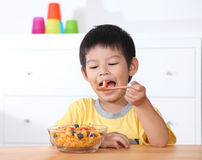 Little asian boy eating breakfast on wooden table in home. Stock Images