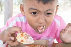 Cute little asian boy eating snack royalty free stock images