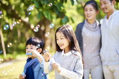 Little asian boy and girl blowing bubbles outdoors royalty free stock photos