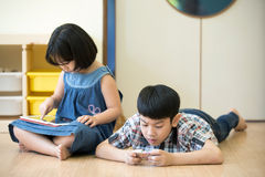 Little Asian boy and girl are playing together with a computer t Stock Image