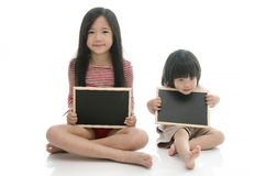 Little asian boy and girl sitting and holding  chalkboard Stock Photo