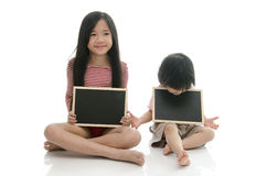 Little asian boy and girl sitting and holding  chalkboard Royalty Free Stock Image