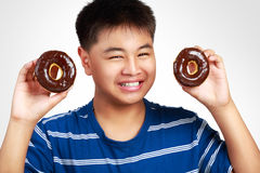 Little asian boy holding a chocolate donuts Royalty Free Stock Image