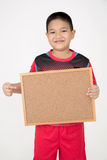 Little asian boy holding empty wood board in sport unifrom Stock Photo