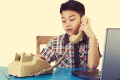 Little asian boy holding old telephone receiver. Stock Images