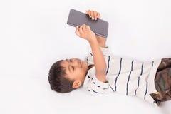 little asian boy lying play tablet on floor Stock Photo