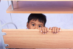 A little asian boy lying under the table Stock Photography