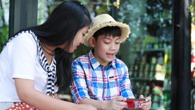 Little asian boy with mobile phone and teenage girl talk together stock video footage