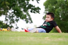 Little asian boy. Outdoor portrait of a little asian fat boy, Play in the park,Sit on the lawn and rest stock images