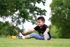 Little asian boy. Outdoor portrait of a little asian fat boy, Play in the park,Sit on the lawn and rest stock image