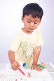 little asian boy paint color on white paper Stock Photos