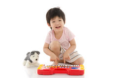 Little asian boy playing electrical toy piano Royalty Free Stock Photography
